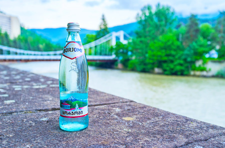 BORJOMI, GEORGIA - MAY 27, 2016: The bottle of Borjomi mineral water on the bank of Kura river with the white bridge of Beauty on the background, on May 27 in Borjomi. Publikacyjne