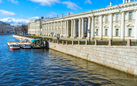 The stone embankment of Fontanka River with the side wall of Baroque Anichkov Palace and the station of the pleasure boats, waiting for tourists, St Petersburg, Russia. Editorial