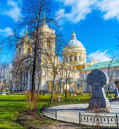SAINT PETERSBURG, RUSSIA - APRIL 25, 2015: The memorial cross in garden of Alexander Nevsky Lavra and the Holy Trinity Cathedral behind the trees, on April 25 in Saint Petersburg.