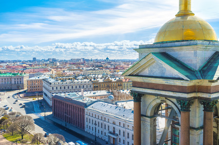 The view on the luxury mansions of St Isaacs Square and old roofs of St Petersburg from the rooftop of St Isaacs Cathedral with its golden domed bell tower on the foreground, Russia.