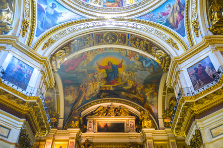 SAINT PETERSBURG, RUSSIA - APRIL 25, 2015: The splendid rich interior of St Isaacs Cathedral includes painted and mosaic icons, covering walls and ceiling, surrounded by carved gilt ornaments and old slavonic inscriptions, on April 25 in Saint Petersburg