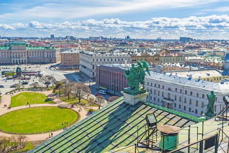 The bronze sculpture of St Matthew the Apostle with Angel on the St Isaacs Cathedrals roof overlooks the St Isaacs Square, St Petersburg, Russia. Stock Photo