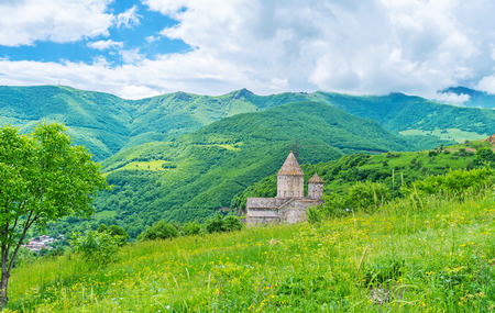 The St Peter and Paul Cathedral of Tatev Monastery is seen behind the hilly green meadow, covered with wildflowers, Syunik Province, Armenia. Stock Photo