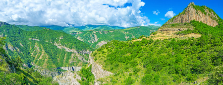 tatev: The Vorotan river gorge with the massive basalt outputs, lush greenery on the steep slopes and medieval Tatev Monastery on the distance, Halidzor, Syunik Province, Armenia.