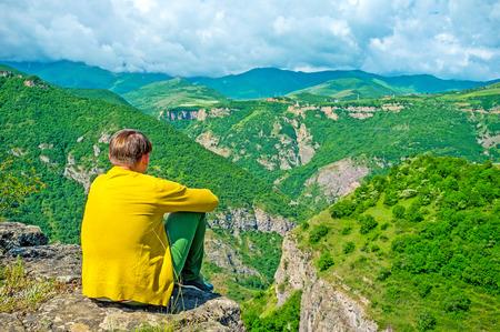 El joven solo se sienta sobre el precipicio y disfruta de la naturaleza de la provincia de Syunik, Halidzor, Armenia.