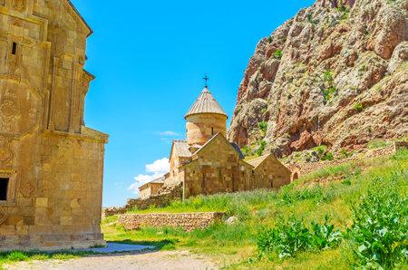 monasteri: La Chiesa rinnovata Surb Karapet (San Giovanni Battista) con la roccia rossa sullo sfondo, Monastero Noravank, Vayots Dzor, Armenia.