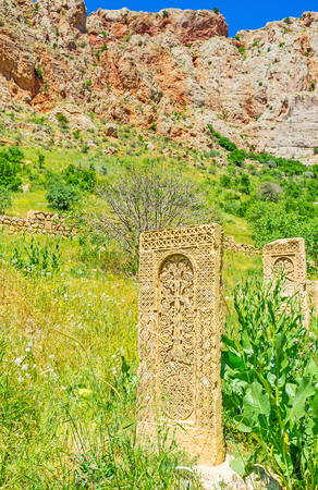 The old khachkars of Noravank monastery with the red rocky slope of Amaghu canyon on the background, Vayots Dzor Province, Armenia. Stock Photo