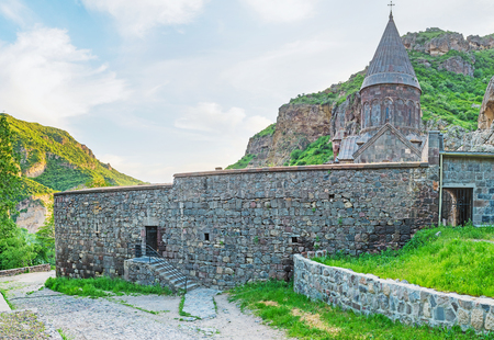 The Geghard Monastery surrounded by massive fortress wall and located on the slope of Azat River Gorge, Kotayk Province, Armenia.
