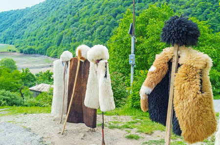papakha: The Georgian shepherds costume - the hat (papakha) and coat of sheeps fur are the best choice for cold mountain weather, Ananuri, Georgia.