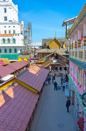 doubleheaded: MOSCOW, RUSSIA - MAY 10, 2015: The covered stalls of Vernissage Market in Izmailovo with the timbered building of art workshop in front, on May 10 in Moscow.