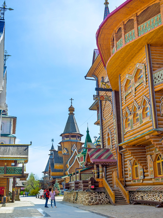 MOSCOW, RUSSIA - MAY 10, 2015: The timbered wall of Tsars Palace in Izmailovsky Kremlin with the St Nicholas Church on the background, on May 10 in Moscow.
