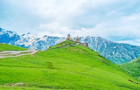 The Tsminda Sameba (Holy Trinity) Church in Gergeti is the important point in trackers routes, going to Kazbek Mount, Georgia. 版權商用圖片 - 66861584