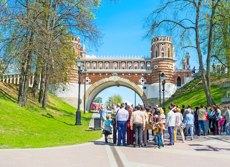 MOSCOW, RUSSIA - MAY 10, 2015: The groups of tourists at the Figured (Shaped) Bridge in Tsaritsyno Park, also serving as the gate, leading to the Royal Palace, on May 10 in Moscow.