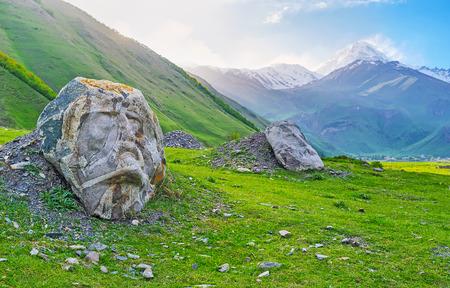 The stone faces of famous Georgian writers and poets on the green meadow of Sno village, Kazbegi, Georgia. Stockfoto