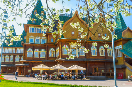 tsar: The timbered Grand Palace of Tsar Alexei Mikhailovich in Kolomenskoye Manor with the summer cafe on the foreground through the blooming branches, Moscow, Russia. Editorial