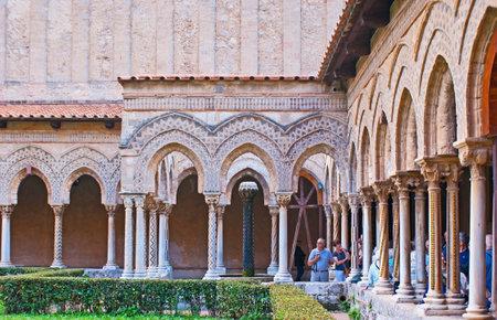 arcos de piedra: Monreale, Italia - 10 de octubre, 2016: El zigzag negro tallado columna de la antigua fuente árabe en el jardín del Claustro de Monreale, rodeado de pintorescos arcos de piedra, el 10 de octubre en Monreale.