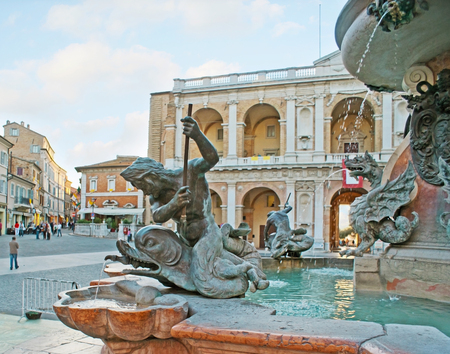 LORETO, ITALY - OCTOBER 6, 2012: The great fountain in Madonna Square decorated with bronze tritons, dolphins, winged serpents and coats of arms, on October 6 in Loreto.