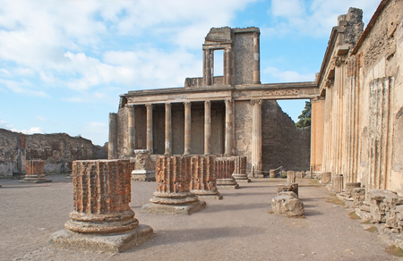 The ruins of Jupiter Temple with the massive green columns in front of it, Pompeii, Italy.