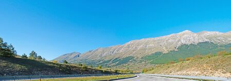 The highway opens view on the slopes of Gran Sasso Mountain Range, part of  Apennines, located in Abruzzo, Italy.