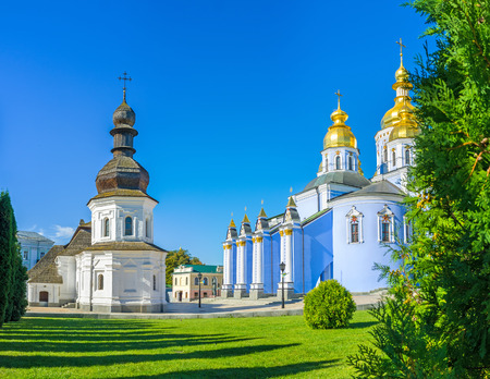 The old Refectory of St John the Divine and painted Cathedral of St Michaels Golden-Domed Monastery surrounded by green garden, Kiev, Ukraine.