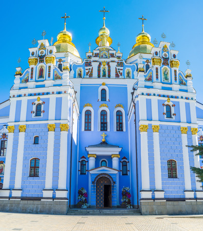 The bright blue facade of Cathedral of St Michaels Golden-Domed Monastery decorated with fretwork, colorful traceries, icons and shining golden onion domes, Kiev, Ukraine.