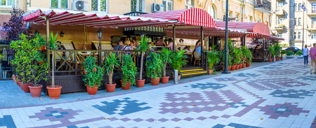 KIEV, UKRAINE - SEPTEMBER 8, 2016: The lovely outdoor cafe at the Golden Gate and Zolotovorotsky park, in the street, decorated with Ukrainian traditional pattern on the road, on September 8 in Kiev. Editorial
