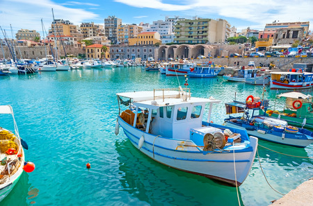 HERAKLION, GREECE - OCTOBER 16, 2013: The lazy fishing boats slowly ride on the waves in old harbor, on October 16 in Heraklion.