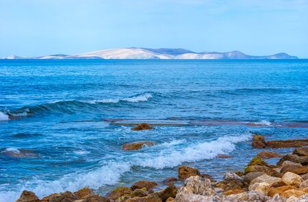 The gentle waves at the rocky shore of Herklion, Crete, Greece. Stock Photo