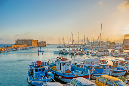 HERAKLION, GREECE - OCTOBER 13, 2013: The bright sunrise over the inner harbor, guarded by Venetian fortress, named Rocca al Mare, and full of yachts and fishing boats, on October 13 in Heraklion.