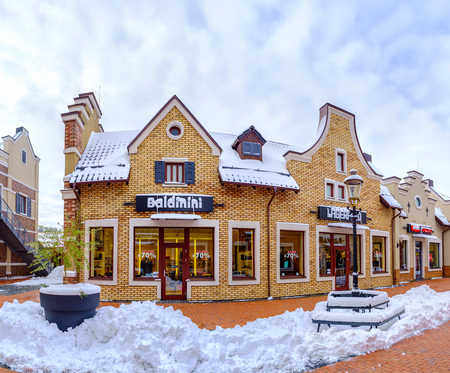 KIEV, UKRAINE - NOVEMBER 11, 2016: The boutiques of the Dutch style outlet city covered with snow and prepare for holiday sales, on November 11 in Kiev.