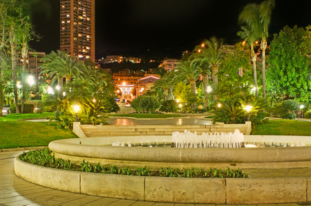 The evening walk in French style gardens of Monte Carlo, locted opposite the Casino Square, Monaco. Stock Photo