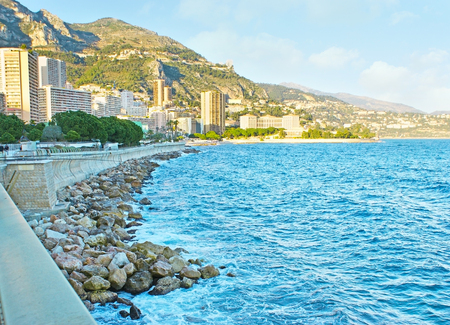 The Boulevard of Loui II is the seaside promenade of Monaco, overlooking Monte Carlo high-rises, greenery of Japanese garden and the green coast of Mediterranean sea.