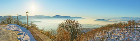 Panorama of the snowy promenade, overlooking the foggy Orestiada Lake and winter mountains, surrounding Kastoria, Greece.