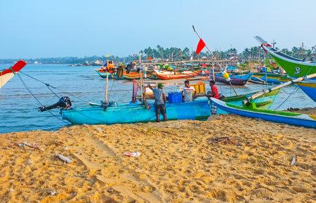 HIKKADUWA, SRI LANKA - DECEMBER 5, 2016: The fishermen moor the boat at the old fishing harbor, on December 5 in Hikkaduwa.