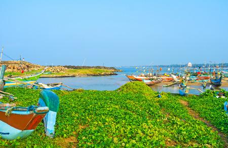 The old colorful fishing catamaran-boats in harbor of Hikkaduwa, Sri Lanka.