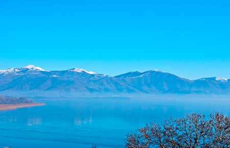 The icy Orestiada Lake reflects bright blue sky and foggy mountains, Kastoria, Greece.