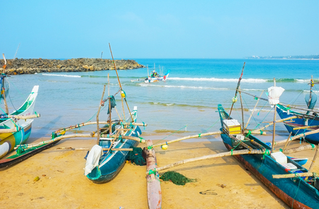 HIKKADUWA, SRI LANKA - DECEMBER 5, 2016: The fishing port is full of traditional catamaran-boats, on December 5 in Hikkaduwa.