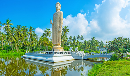 The Buddha Statue on the tiny island, connected with the river bank by the small bridge, guarded by two white lions, Peraliya, Sri Lanka. Stock Photo