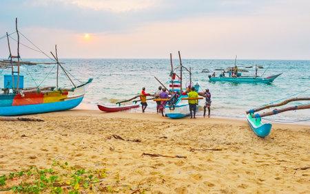 HIKKADUWA, SRI LANKA - DECEMBER 5, 2016: The last boats back from the evening fishing and fishermen steer them on the sand, on December 5 in Hikkaduwa.