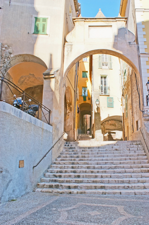 menton: The staircase and decorative medieval gate located between the Square of Saint-Michel and Mattoni street in old Menton, France.