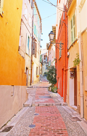 menton: The narrow hilly street with the colorful houses and old-fashioned lanterns, Menton, France. Stock Photo