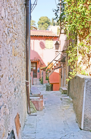 menton: The narrow street leads to the bright pink house, surrounded by stone walls, Menton, France.