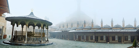 KONYA, TURKEY - JANUARY 20, 2015: The courtyard of Mevlana Museum with the view on the living chambers of dervishs and the silhouette of the Selimiye Mosque in fog, on January 20 in Konya.
