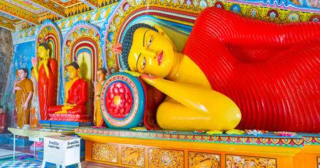 ANURADHAPURA, SRI LANKA - NOVEMBER 26, 2016: The Reclining Buddha in Isurumuniya Rock Temple, with the smaller figures next to him, on November 11 in Anuradhapura.