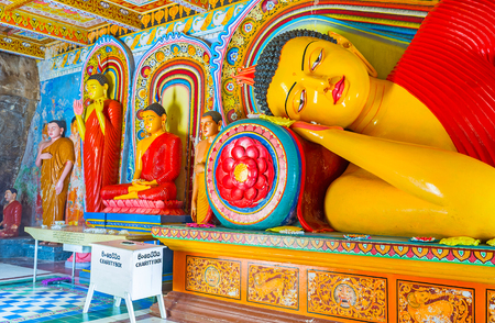 ANURADHAPURA, SRI LANKA - NOVEMBER 26, 2016: The statues of Buddha in Isurumuniya Rock Temple painted in bright colors and surrounded by floral patterns, on November 11 in Anuradhapura.