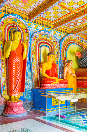 ANURADHAPURA, SRI LANKA - NOVEMBER 26, 2016: Interior of Isurumuniya Rock Temple with statues of Standing and Seated Buddha in poses of offer protection and meditation, on November 11 in Anuradhapura.
