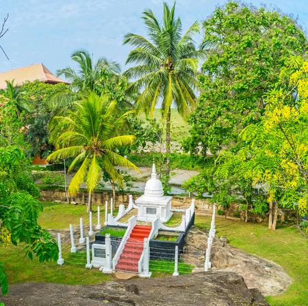 The white Buddhist Stupa is hidden in lush garden of Isurumuniya Temple, Anuradhapura, Sri Lanka.