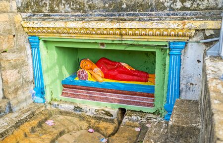 The statue of Reclinng Buddha in niche on the Rock of Isurumuniya Temple, Anuradhapura, Sri Lanka.