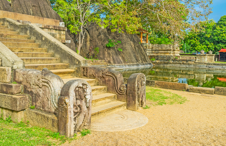 The staircase to the Rock Temple in Isurumuniya decorated with carved sculptures and the carved semi-circular stone slab - moonstone in front of it, Anuradhapura, Sri Lanka.