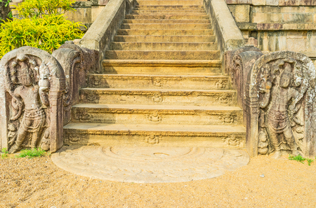 temple tank: The carved staircase in Isurumuniya Rock Temple with the semi-circular stone slab -moonstone (sandakada pahana), patterns and dwarves on the stairs and the sculptures from both sides, Anuradhapura, Sri Lanka.